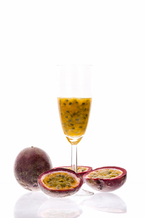 champagne flute: Juicy fruit pulp of purple passion fruit presented in its hard outer rind and in a champagne flute. Sweet sour cocktail and tropical delight. Studio shot over white background and reflective surface.