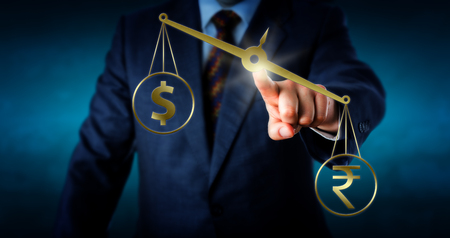 canadian dollar: Indian rupee currency symbol is outbalancing the US or Canadian dollar sign on a golden weight scale. A trader is touching the center of the slanting virtual balance. Metaphor for the forex market.