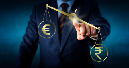 eurozone: Indian rupee symbol is outbalancing the European union currency sign on a golden pair of scales. Metaphor for trade imbalance and foreign currency exchange between the euro zone and India.