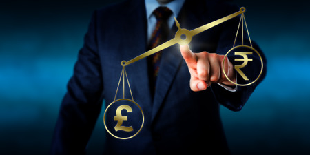outweighing: British pound sterling is outweighing the Indian rupee sign on a golden pair of balances. Business concept for trade deficit, the modern foreign exchange market and international forex trading. Stock Photo