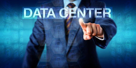 technology metaphor: IT manager is pressing the word DATA CENTER on a touch screen interface. Technology metaphor and business concept for data center operations and information technology infrastructure management.