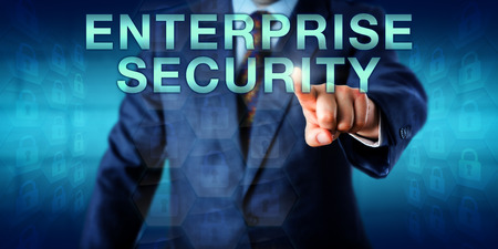 Manager is pressing ENTERPRISE SECURITY on a touch screen interface. Business metaphor and technology concept for security processes and information security systems throughout the entire enterprise. Stock Photo
