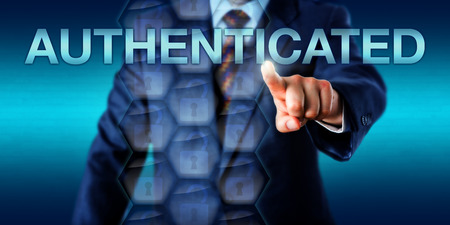 capitalized: IT administrator is touching the capitalized word AUTHENTICATED onscreen. Technology metaphor and business concept for authentication procedures and identity proof in network access control.