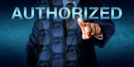 capitalized: Corporate user is touching the capitalized word AUTHORIZED onscreen. Technology concept and business metaphor for authorized computing access or a user granted authority to access information.