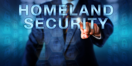 homeland: Professional pushing HOMELAND SECURITY on a touch screen. Business metaphor, security industry term and technology concept for the protection of a national territory, population and infrastructure.