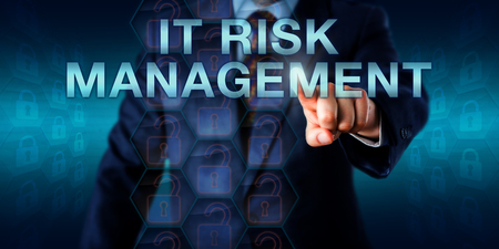 Consultant pushing IT RISK MANAGEMENT on a touch screen interface. Business metaphor and technology concept for a systematic approach to risk identification and management of information technology. Stock Photo