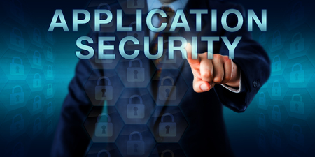 securing: Executive user pushing APPLICATION SECURITY onscreen. Business and technology concept for security policy of a software application, the prevention of flaws in its design and securing of a network. Stock Photo