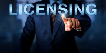 licensing: Management consultant or proprietor pushing LICENSING on a touch screen interface. Business concept and technology metaphor. Plenty of copy space over blue business suit and blurred office interior.