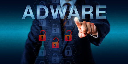 adware: Marketing manager pressing ADWARE on a screen. Three unlocked padlock icons are popping up in a hexagonal coding matrix signifying the presence of advertising-supported software. Technology concept.