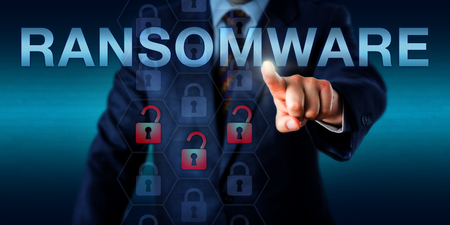 Manager is pushing RANSOMWARE on a touch screen. Three opened lock icons light up in a hexagonal code structure signifying an infected computer system or application. Security technology concept. Stock Photo