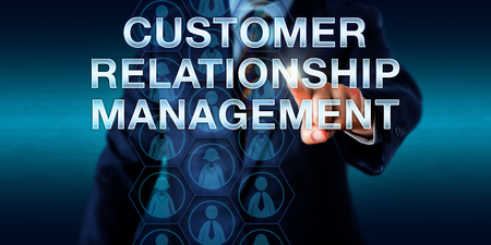 signify: Business manager is touching CUSTOMER RELATIONSHIP MANAGEMENT onscreen. Business concept and technology metaphor. Male and female customer icons embedded in hexagons do signify collected client data. Stock Photo