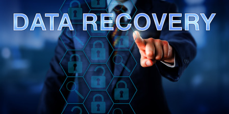 Manager is pointing at DATA RECOVERY on a touch screen. Business metaphor and technology concept. Magnifier glass icons do reference analyzing tools and locked padlocks represent encrypted files. Stock Photo