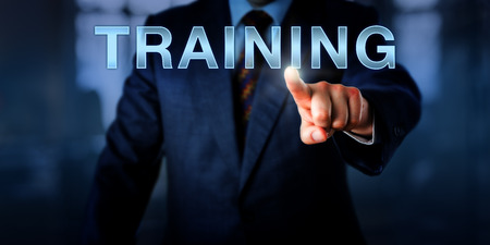 qualify: Corporate human resources manager is pressing TRAINING on a touch screen interface. Business concept for continued professional development, life-long learning and improvement of performance.
