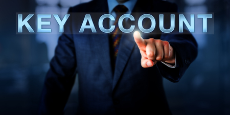 account executive: Sales manager is pushing KEY ACCOUNT on a touch screen. Business metaphor and concept for customer relationships with the most profitable clients that account for the majority of company revenue. Stock Photo