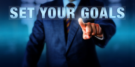 Business coach is touching the phrase SET YOUR GOALS on a screen. Business concept and coaching catch phrase for the definition and work towards desired personal and organizational results.