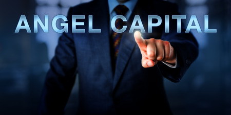 patronage: Business executive is pointing at ANGEL CAPITAL on a touch screen. Financial concept and business metaphor for investment funds provided under extremely high risk by seed or informal investors.