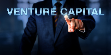 phrase novel: Angel investor is touching VENTURE CAPITAL on a virtual screen. Finance metaphor and business concept for private equity funding, angel investing under high risk and institutional capital funding. Stock Photo