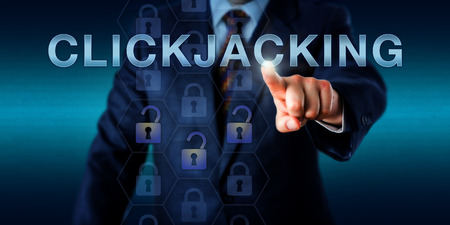 concealed: Business executive is touching CLICKJACKING on a virtual screen. Information technology and cybersecurity concept for a user interface redress attack via embedded code and malicious script. Stock Photo