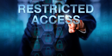 access restricted: Business user pushing RESTRICTED ACCESS on a touch screen interface. Information technology concept for data security mechanisms, encryption software and ransomware scams locking down computer files.