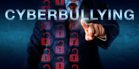 harming: Anonymous white collar cyberbully pressing CYBERBULLYING on a touch screen interface. Information technology and cyber security concept for hostile and repeated actions aimed at defaming and harming.