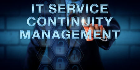 reducing: Business continuity manager touching IT SERVICE CONTINUITY MANAGEMENT on a virtual screen. Information technology concept for processes and contingency planning reducing the risk of an IT disaster. Stock Photo