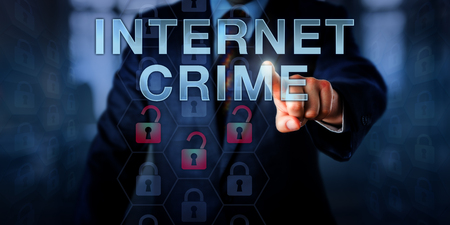 fraud: White collar hacker is pushing INTERNET CRIME on a touch screen interface. Information technology metaphor and security concept for computer crime perpetrated online via a computer and a network.