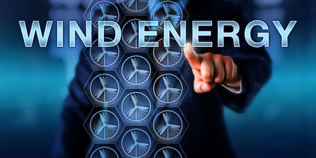business metaphor: Mechanical engineering consultant is touching WIND ENERGY on a virtual screen. Business metaphor and technology concept for electric power generation via the renewable energy source of wind. Stock Photo