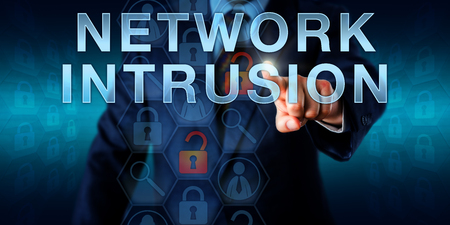 intruder: Cybercriminal intruder touching NETWORK INTRUSION on a virtual screen. Information technology metaphor and security concept for harmful attacks and malicious violations within a network or system.