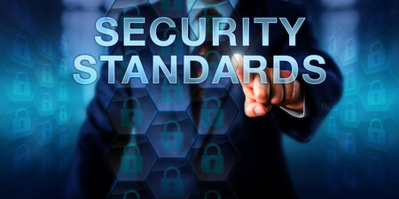signify: Manager is pressing SECURITY STANDARDS on a touch screen interface. Information technology and computer security concept. Locked padlock icons in a uniform layout signify standard implementation.