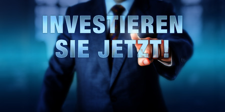leverage: Businessman is pressing INVESTIEREN SIE JETZT! on a touch display interface. German language call to action meaning DO INVEST NOW. Virtual text on a transparent visual screen. Financial concept.