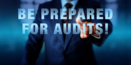 audits: Male Chief Information Security Officer is touching the phrase BE PREPARED FOR AUDITS! on a visual screen. Business challenge metaphor and information technology concept for audit-readiness. Stock Photo