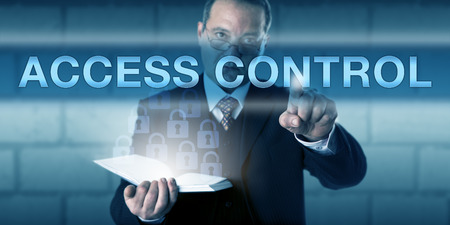 countenance: Security administrator pressing ACCESS CONTROL on a virtual screen. Dressed in smart business suit, the business man is glancing across his glasses with a focused countenance. IT security concept.