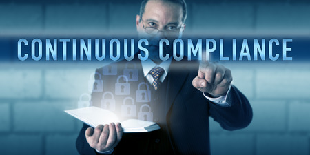Security director or CISO is touching CONTINUOUS COMPLIANCE on a visual interactive screen. Business metaphor and information technology concept for best practice workflow and audit-readiness. Stock Photo