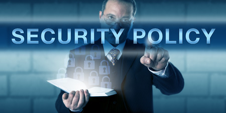 standards: CISO with a critical look across his glasses is pushing SECURITY POLICY on a visual screen. Business challenge metaphor and information technology concept network protection standards and procedures. Stock Photo