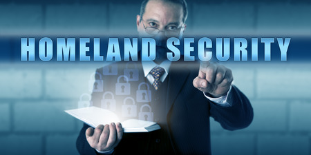 preparedness: Governmental protection professional is pushing HOMELAND SECURITY on a virtual touch screen. Business metaphor and security industry concept for emergency preparedness and threat prevention.