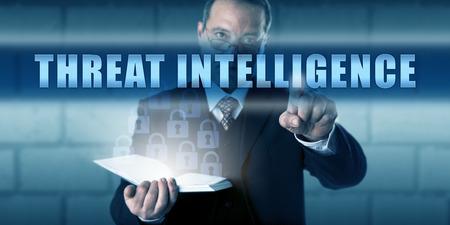 agent de sécurité: Agent de sécurité poussant MENACE INTELLIGENCE sur un écran tactile translucide. métaphore d'affaires et le concept de la sécurité informatique. regard concentré sur les lunettes et le geste décisif pointant la main.