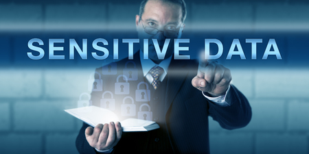 private information: Security director pressing SENSITIVE DATA on a virtual touch screen interface. Business metaphor and information technology concept for confidential information sharing in a protected IT environment. Stock Photo