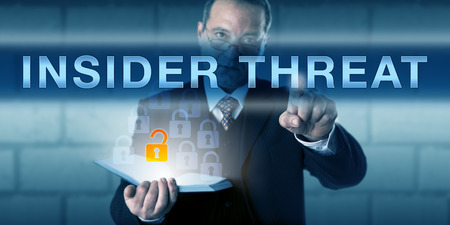 insider information: White collar employee is pressing INSIDER THREAT on a virtual touch screen interface. Business challenge metaphor and information technology concept for an insider-caused data loss. Stock Photo