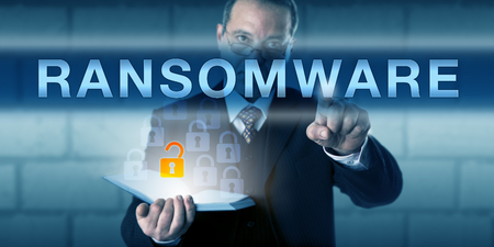 restricting: Security consultant is touching RANSOMWARE on a virtual interactive screen. Business metaphor and information technology concept for malware restricting system access for the victimized user.
