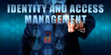 logon: Business manager is touching IDENTITY AND ACCESS MANAGEMENT on an interactive visual screen. Stock Photo