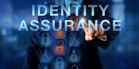 credential: Administrator pressing IDENTITY ASSURANCE on an interactive touch screen display. Stock Photo