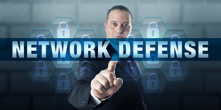 cyber attacks: Manager is pressing NETWORK DEFENSE on a touch screen interface. Business metaphor and information technology concept for the protection of corporate network infrastructure against cyber attacks. Stock Photo