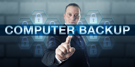 backup: Data manager pushing COMPUTER BACKUP on a virtual touch screen interface. Stock Photo