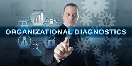 Corporate consultant is pressing ORGANIZATIONAL DIAGNOSTICS on an interactive touch screen.