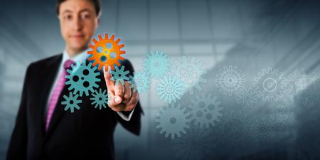 Happy businessman is touching a cog in a virtual gear train.
