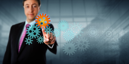 computer services: Happy businessman is touching a cog in a virtual gear train.