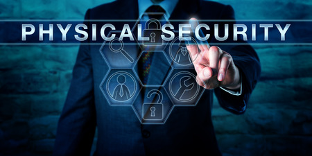 id theft: Intelligence officer is pushing PHYSICAL SECURITY on an interactive transparent control screen. Business metaphor and technology concept. Application icons with security tools arranged in a cycle.