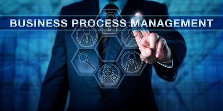 strategic focus: Male executive is pressing BUSINESS PROCESS MANAGEMENT on an interactive touch screen display. Business metaphor and technology concept for a strategic focus on corporate performance as an asset.