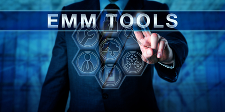 business metaphor: Corporate manager pressing EMM TOOLS on an interactive touch screen interface. Business metaphor and mobile technology concept for enterprise mobility management under a bring your own device policy.