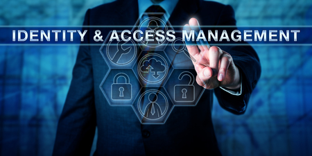 identity management: Manager pushing IDENTITY & ACCESS MANAGEMENT on a virtual interactive touch screen. Business metaphor and computer security procedure concept for technology enabling access to authenticated users. Stock Photo